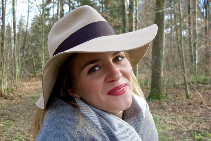 Smiling blonde fashion and style blogger girl in closeup view with floppy hat and red lips in the woods