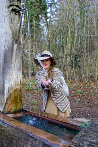 Smiling blonde fashion and style blogger girl with floppy hat and plaid jacket splashing water in the woods
