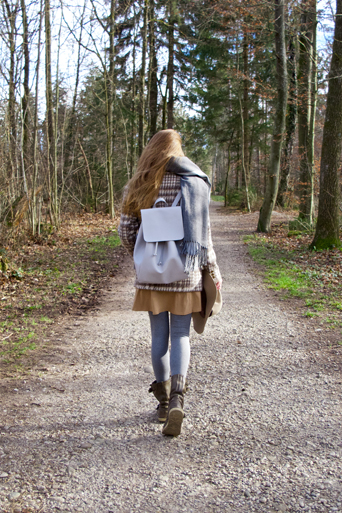 Fashion and style blogger girl from behind with plaid jacket and backpack in the woods