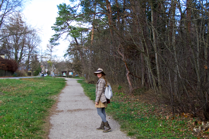 Fashion and style blogger girl with floppy hat, plaid jacket and backpack walking in the woods