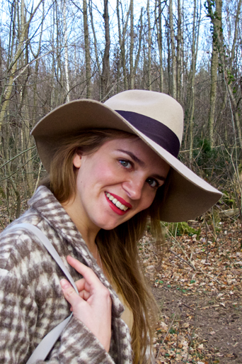 Smiling fashion and style blogger girl in closeup view with floppy hat, plaid jacket and red lips in the woods