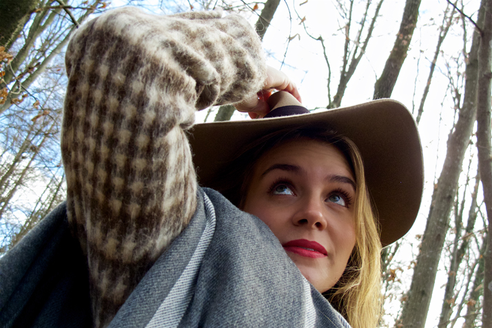 Blonde fashion and style blogger girl in closeup view with floppy hat, oversized scarf and red lips in the woods