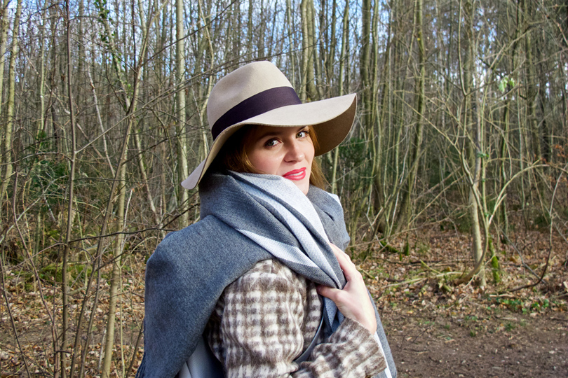 Smiling blonde fashion and style blogger girl in closeup view with floppy hat, oversized scarf, plaid jacket and red lips in the woods