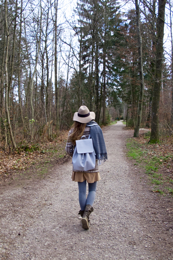 Fashion and style blogger girl from behind with floppy hat and backpack in the woods