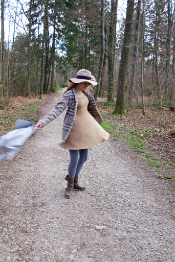 Fashion and style blogger girl dancing with floppy hat and backpack in the woods