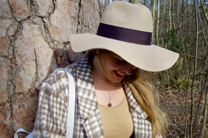 Smiling fashion and style blogger girl in closeup view with floppy hat in the woods