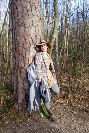 Fashion and style blogger girl with oversized scarf, plaid jacket, floppy hat and backpack in the woods