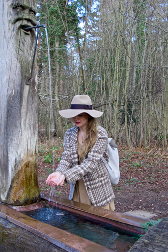 Fashion and style blogger girl with plaid jacket and floppy hat in the woods getting water