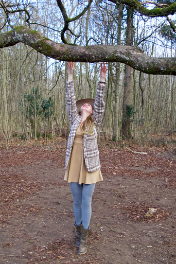 Blonde fashion and style blogger girl with floppy hat and plaid jacket trying to reach a high branch in the woods