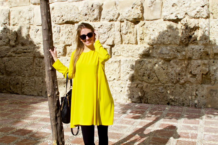 Smiling fashion and style blogger girl wearing a colorful, yellow dress, black Michael Kors bag and glossy loafers in the beautiful old town of Marbella