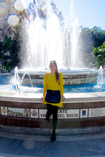 Blond fashion and style blogger girl sitting on a fountain in Marbella, wearing a colorful, yellow dress, black Michael Kors bag and glossy loafers