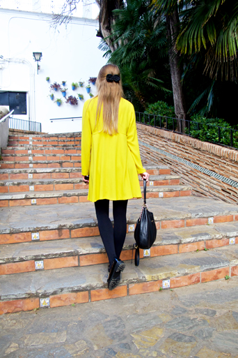 Blond fashion and style blogger girl from behind wearing a colorful, yellow dress, black Michael Kors bag and glossy loafers