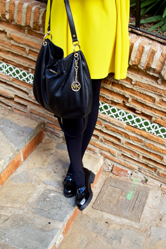 Fashion and style blogger girl wearing a colorful, yellow dress, black Michael Kors bag and glossy loafers in closeup view