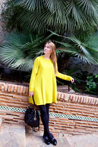Fashion and style blogger girl wearing a colorful, yellow dress, black Michael Kors bag and glossy loafers