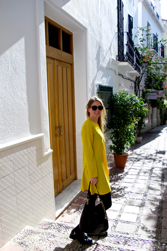 Smiling fashion and style blogger girl wearing a colorful, yellow dress, sunglasses, black Michael Kors bag and glossy loafers in a beautiful alley in the old town of Marbella