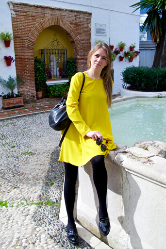 Blonde fashion and style blogger girl sitting on a fountain, wearing a colorful, yellow dress, black Michael Kors bag and glossy loafers