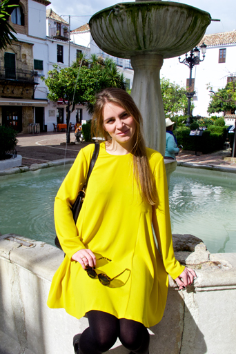 Blond fashion and style blogger girl sitting on a fountain, wearing a colorful, yellow dress, black Michael Kors bag and glossy loafers