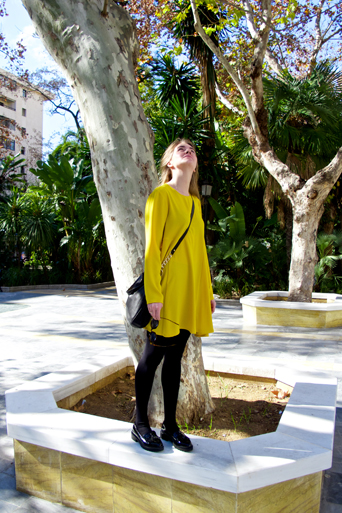 Blond fashion and style blogger girl looking up in the air, wearing a colorful, yellow dress, black Michael Kors bag and glossy loafers surrounded by trees and palm trees