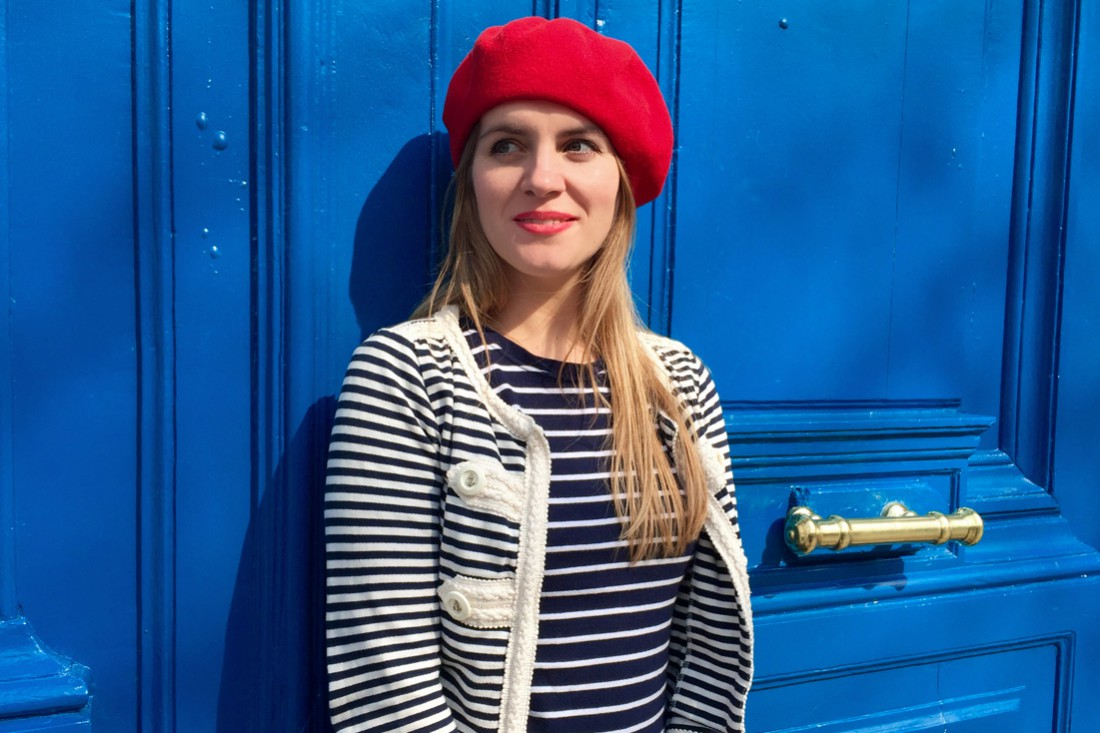 Smiling blonde fashion and style blogger girl in closeup view wearing different stripes, red béret and red lipstick in front of a blue door