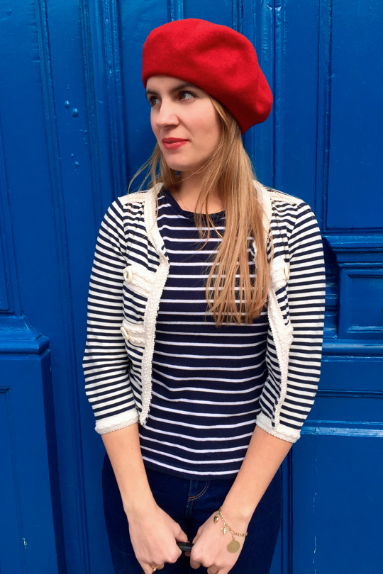Blond fashion and style blogger girl in closeup view wearing different stripes, red béret and red lipstick in front of a blue door