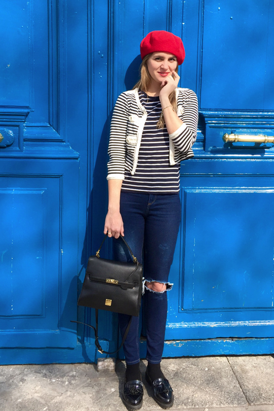 Blonde fashion and style blogger girl wearing different stripes, red béret, destroyed jeans, glossy loafers, MCM bag and red lipstick in front of a blue door