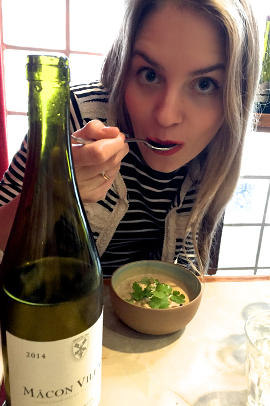 Blonde fashion and style blogger girl eating a girasole soup, wearing different stripes and red lipstick