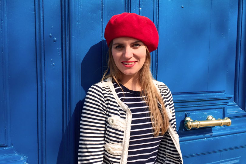 Smiling blond fashion and style blogger girl in closeup view wearing different stripes, red béret and red lipstick in front of a blue door