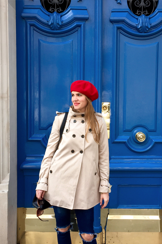 Smiling blonde fashion and style blogger girl in closeup view wearing a trenchcoat, red béret and red lipstick in front of a blue door