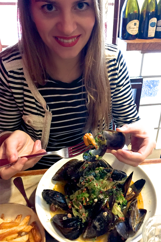 Smiling blond fashion and style blogger girl eating blue mussels, wearing different stripes and red lipstick