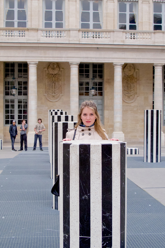 Blonde fashion and style blogger girl standing behind a pillar at the Palais Royal in Paris, wearing a denim jacket, trenchcoat, and a MCM bag