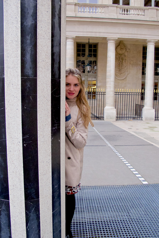 Blonde fashion and style blogger girl hiding behind a pillar at the Palais Royal in Paris, wearing a red flower dress, denim jacket, trenchcoat and glossy loafers