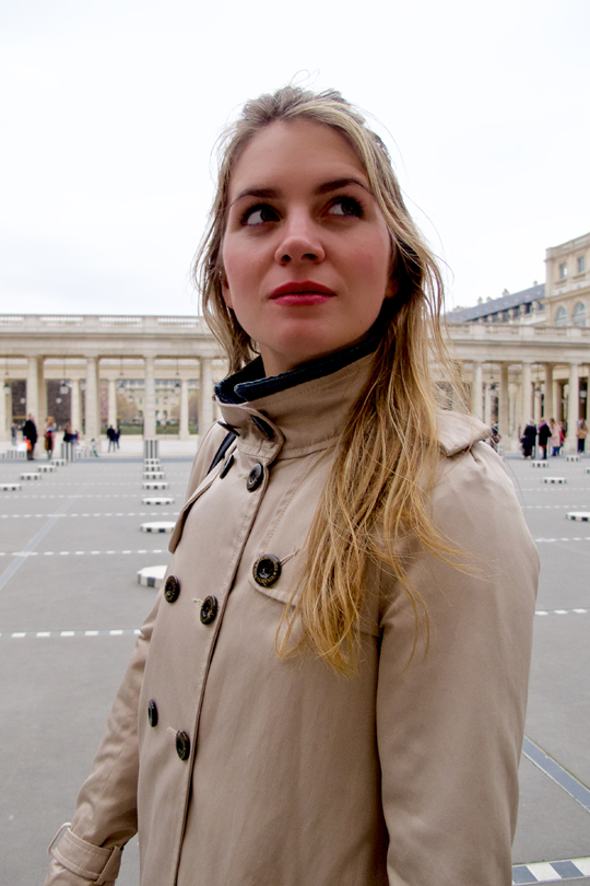 Blond fashion and style blogger girl wearing a denim jacket and a trenchcoat at the Palais Royal in Paris
