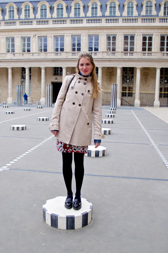 Blond fashion and style blogger girl standing on a pillar at the Palais Royal in Paris, wearing a red flower dress, denim jacket, trenchcoat, glossy loafers and a MCM bag