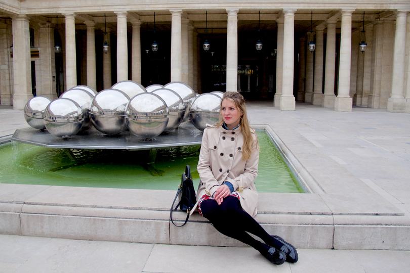 Blonde fashion and style blogger girl sitting on a fountain, wearing a red flower dress, denim jacket, trenchcoat, glossy loafers and a MCM bag at the Palais Royal in Paris