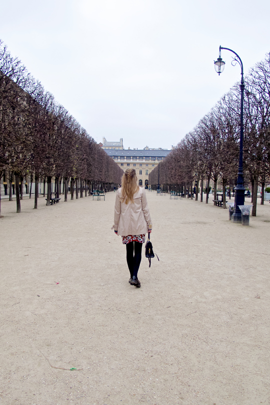 Blonde fashion and style blogger girl walking through an alley of trees in Paris, wearing a red flower dress, trenchcoat, glossy loafers and a MCM bag