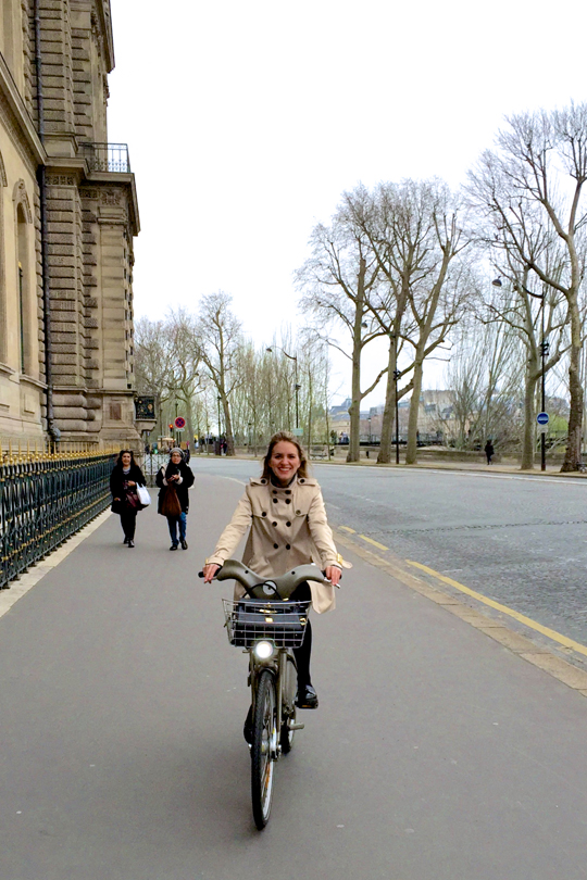 Smiling blonde fashion and style blogger girl riding a bike in Paris, wearing a trenchcoat and glossy loafers