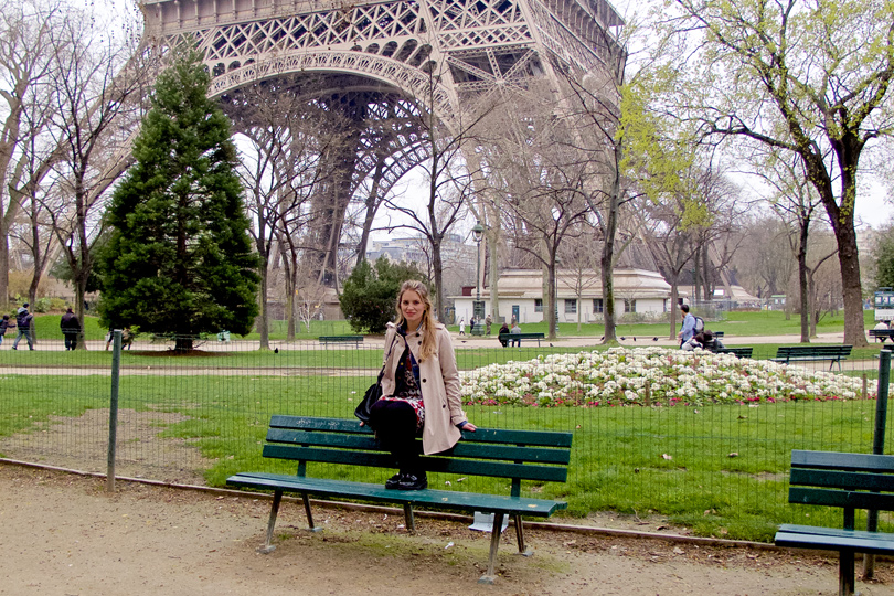 Blonde fashion and style blogger girl sitting on a bench in front of the Eiffel Tower in Paris, wearing a red flower dress, denim jacket, trenchcoat, glossy loafers and a MCM bag