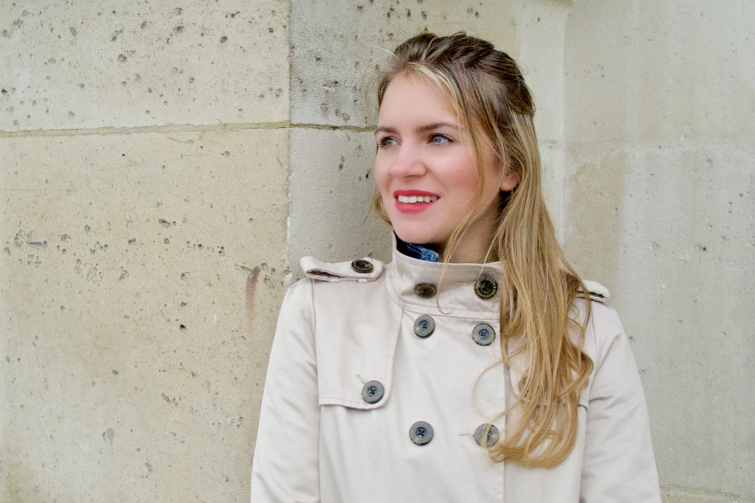 Blonde fashion blogger girl smiling and wearing a trenchcoat