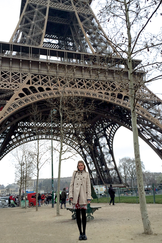 Blond fashion and style blogger girl standing in front of the Eiffel Tower, wearing a red flower dress, denim jacket, trenchcoat, glossy loafers and a MCM bag