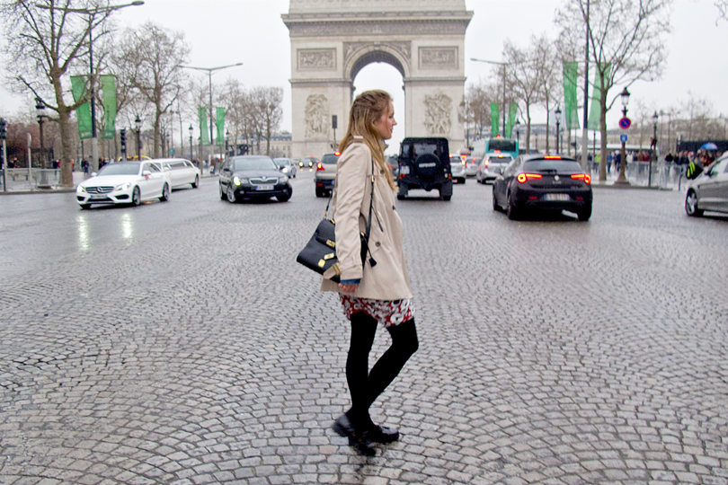 Walking blond fashion and style blogger girl walking in front of the Arc de Triomphe, wearing a red flower dress, denim jacket, trenchcoat, glossy loafers and a MCM bag