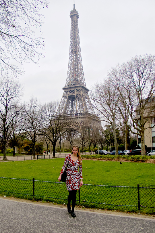 Blond fashion and style blogger girl standing in front of the Eiffel Tower, wearing a red flower dress, glossy loafers and a MCM bag