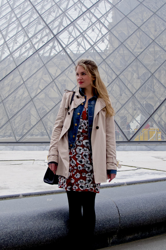 Blond fashion blogger girl standing in front of the Louvre, wearing a red flower dress, a denim jacket and a trenchcoat
