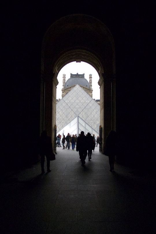 A dark passage with the view of the Louvre outside