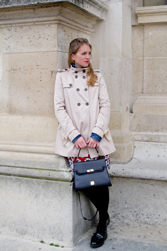 Blond fashion blogger girl leaning on an old building, wearing a red flower dress, denim jacket, trenchcoat, glossy loafers and a MCM bag.