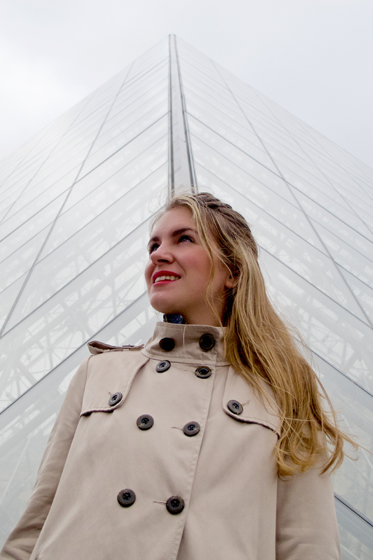 Smiling blonde fashion and style blogger girl in closeup view in front of the Louvre wearing a trenchcoat