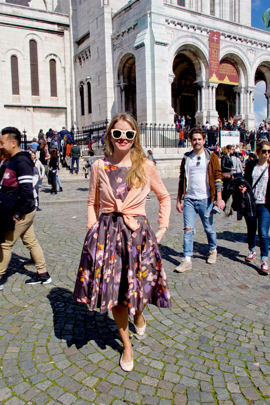 Smiling blonde fashion and style blogger girl walking in front of Sacré-Cœur in Paris, wearing a flower dress, cardigan, sunglasses, ballet flats and a Chanel bag
