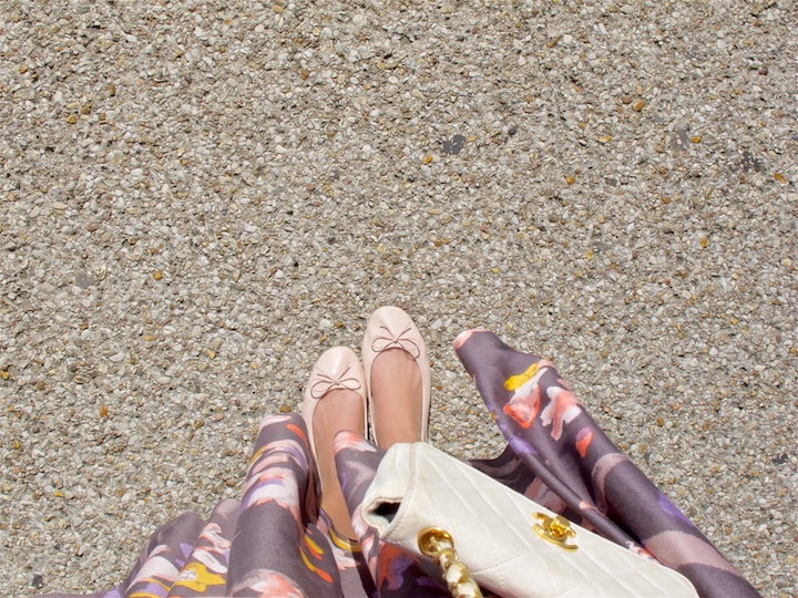Bird's eye view of a fashion and style blogger girl's ballet flats, flower dress and Chanel bag