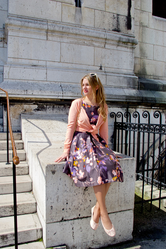 Blond fashion and style blogger girl sitting in front of Sacré-Cœur in Paris, wearing a flower dress, cardigan, sunglasses, ballet flats and a Chanel bag