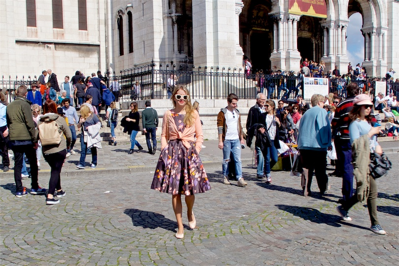 Smiling blond fashion and style blogger girl walking in front of Sacré-Cœur in Paris, wearing a flower dress, cardigan, sunglasses, ballet flats and a Chanel bag