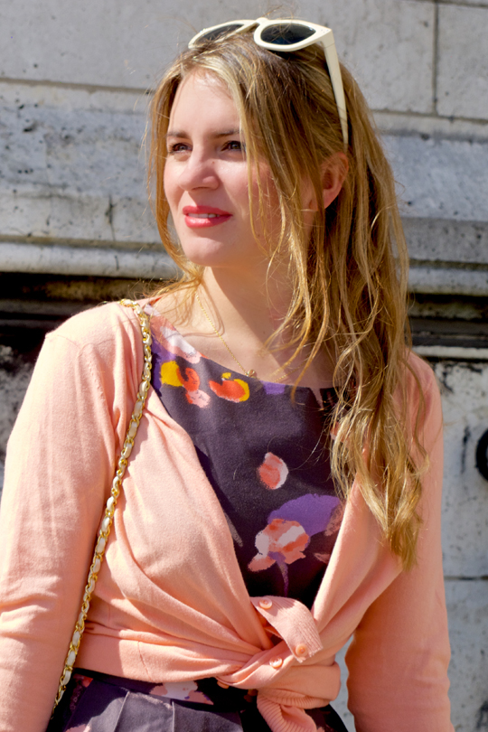 Blond fashion and style blogger girl in closeup view, wearing a flower dress, cardigans, sunglasses and a Chanel bag